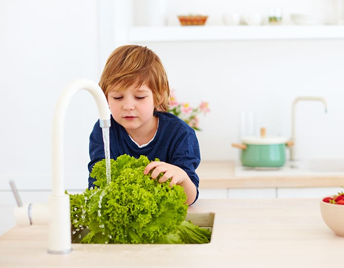 kid washing lettuce leaves under tap water in the kitchen