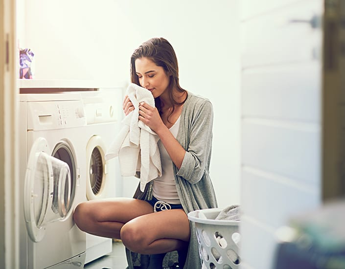 young woman smelling her freshly washed towels